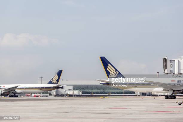 A Boeing Co 777212 aircraft left and a Boeing 777312 aircraft both operated Singapore Airlines Ltd sit on the tarmac at Changi Airport in Singapore...