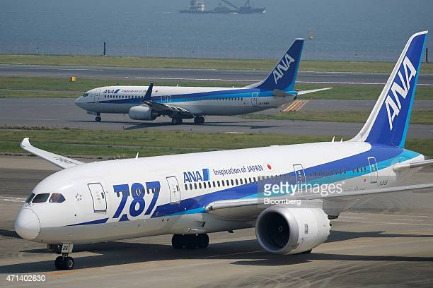 A Boeing Co 787 Dreamliner aircraft bottom and a Boeing 737800 aircraft both operated by All Nippon Airways Co taxi at Haneda Airport in Tokyo Japan...