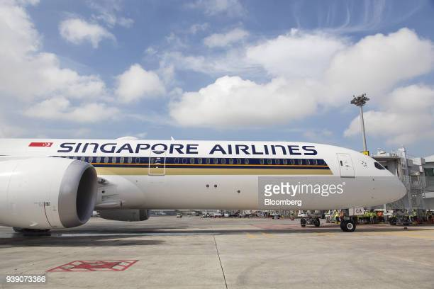 A Boeing Co 78710 Dreamliner aircraft operated by Singapore Airlines Ltd stands docked to a passenger boarding bridge at Changi Airport in Singapore...