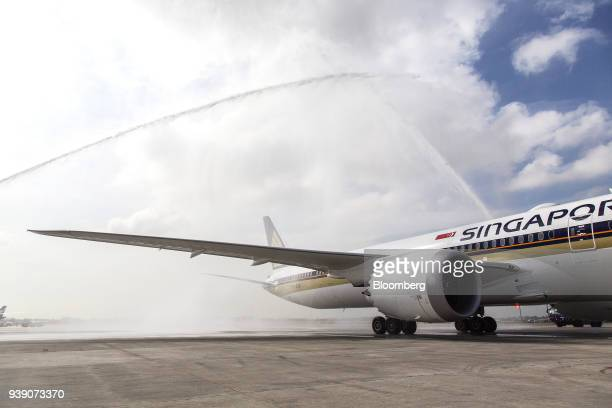 A Boeing Co 78710 Dreamliner aircraft operated by Singapore Airlines Ltd receives a water cannon salute as it arrives at Changi Airport in Singapore...