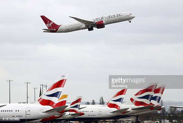 A Boeing Co 7879 Dreamliner passenger aircraft operated by Virgin Atlantic Airways Ltd takes off over a row of passenger aircraft operated by British...