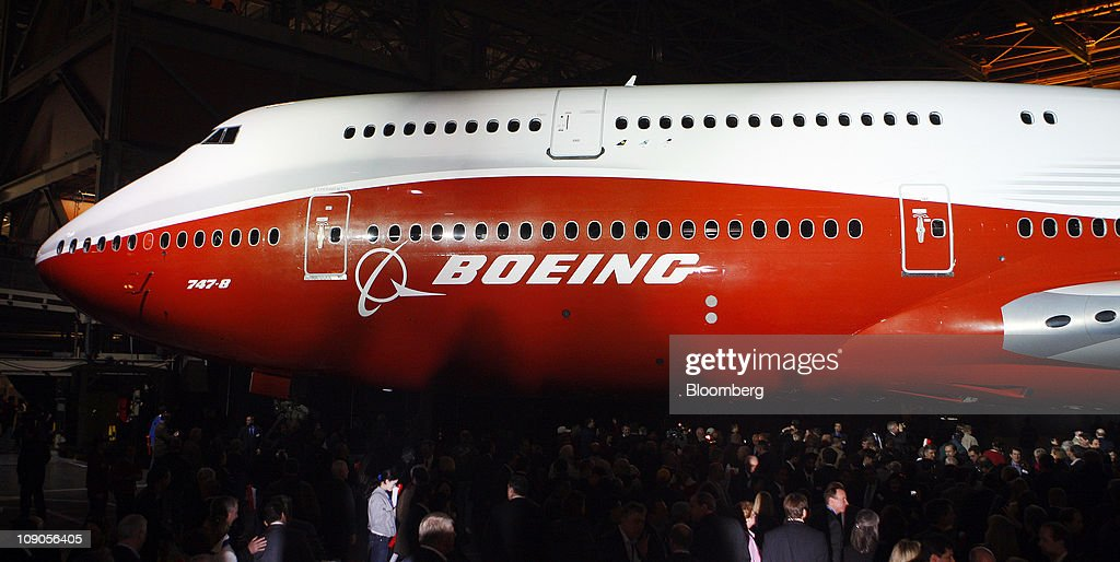 Boeing Co. employees, guests and members of the news media walk around the 747-8 Intercontinental as the jumbo jet is rolled out at Boeing's manufacturing facility in Everett, Washington, U.S., on Sunday, Feb. 13, 2011. Boeing aims for the passenger version of the delayed 747-8 shown to customers and investors today to fly for the first time in March, a little more than a year after the freighter variant. Photographer: Kevin P. Casey/Bloomberg via Getty Images