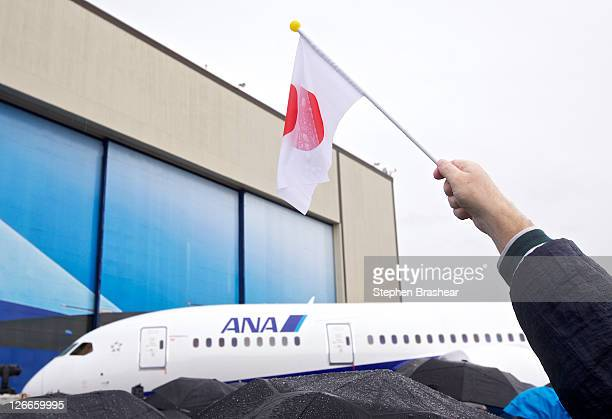 Boeing employee Barry Weber waves a Japanese flag during Boeing's 787 Dreamliner ceremonial first delivery to All Nippon Airways at Paine Field...