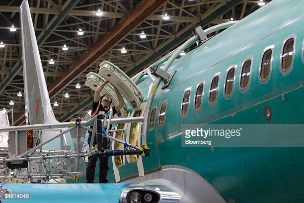 Boeing employee Mike Garcia installs overwing hatch liners on a Boeing 737800 airliner at the company's manufacturing facility in Renton Washington...