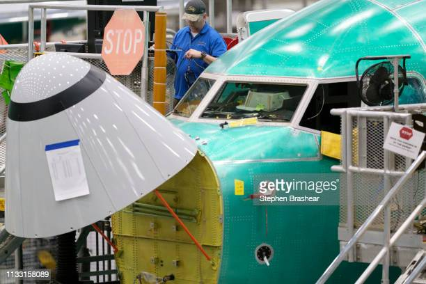 Boeing employees works outside of the cockpit of a Boeing 737 MAX 8 airplane in the company's factory on March 27 2019 in Renton Washington In the...