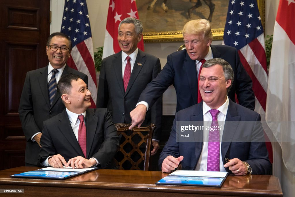 Boeing Executive Vice President Kevin McAllister (R) and CEO of Singapore Airlines Goh Choon Phong (C-L) along US President Donald Trump (C-R) and Lee Hsien Loong (C) of Singapore attend a signing ceremony for airplane sales in the Roosevelt Room at the White House October 23, 2017 in Washington, DC. Trump and Lee are meeting ahead of Trump's first official visit to Asia to attend the APEC and ASEAN meetings during the first two weeks of November.