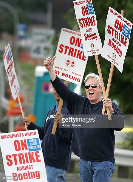 Boeing machinist Michael Glover gestures to passing cars while manning the picket line outside Boeing's plant September 6 2008 in Everett Washington...
