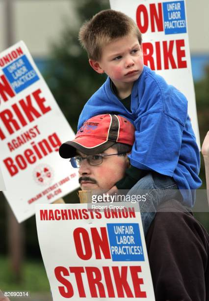 Boeing machinist Scott Green with his son Joshuaon his shoulders walks the picket line outside Boeing's plant September 6 2008 in Everett Washington...