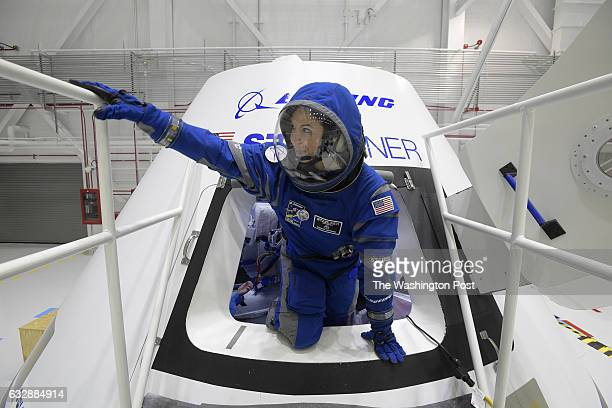Boeing propulsion engineer Monica Hopkins climbs out of a mockup of the CST100 Starliner crew module while wearing a newlydesigned spacesuit during...