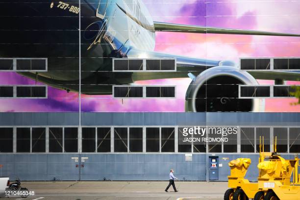 A Boeing worker in a face mask is pictured walking at the Boeing Renton Factory where the Boeing 737 MAX airliners are built in Renton Washginton on...