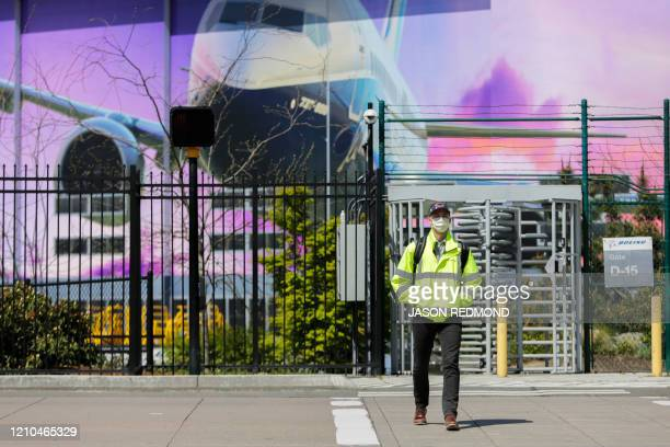 A Boeing worker wears a face mask as he exits the Boeing Renton Factory where the Boeing 737 MAX airliners are built in Renton Washginton on April 20...