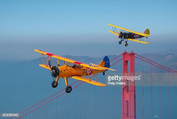 boeing-stearman n2s flying above golden gate - doppeldecker flugzeug stock-fotos und bilder