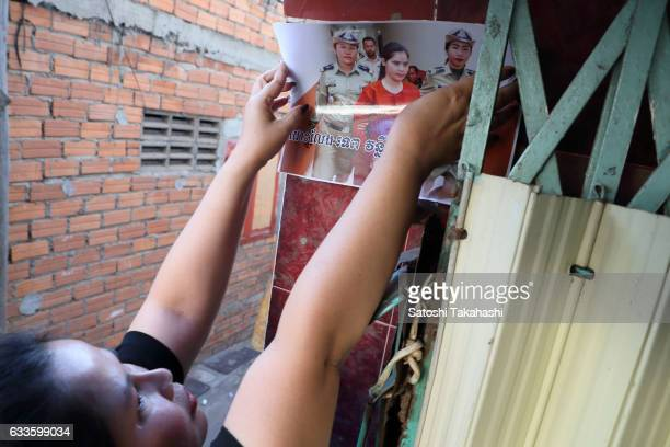 Boeng Kak community activist Bo Chhor Vy sticks the photograph of imprisoned prominent land rights activist Tep Vanny onto the wall calling for the...