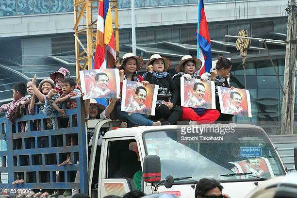 Boeng Kak community activists who hold photographs of slain prominent political analyst Kem Ley during a funeral procession to mark 100 days since...