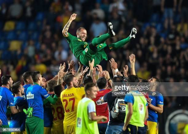 Bogdal Lobont goalkeeper of Romania is thrown in the air by team colleagues as he marked the final of his football playing career after the...