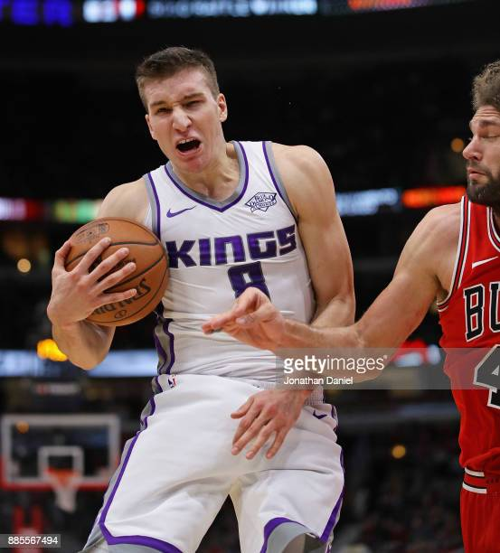 Bogdan Bogdanovic of the Sacramento Kings rebounds next to Robin Lopez of the Chicago Bulls at the United Center on December 1 2017 in Chicago...