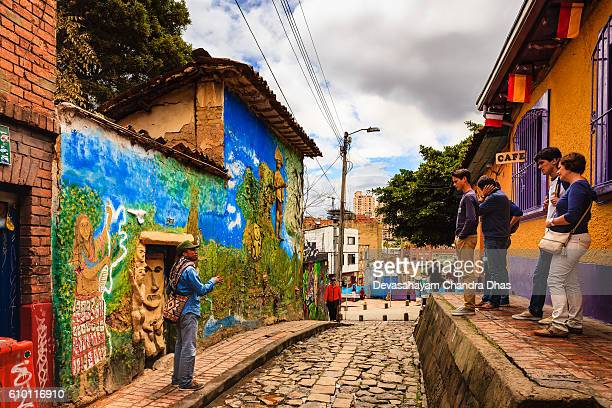Bogotá, Colombia - A Tour Guide Explains A Legend To Tourists on the Narrow, Colorful, Cobblestoned Calle del Embudo In The Historic La Candelaria District