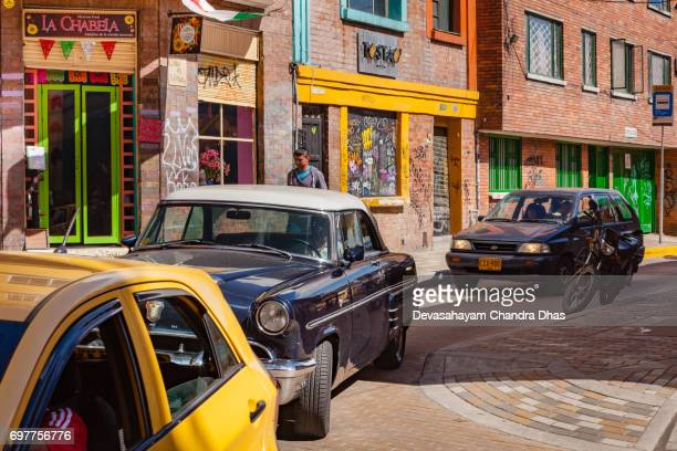Bogotá, Colombia - Bumper to Bumber Traffic Drives Down a Narrow Street in the Historic La Candelaria District of the Andean Capital City