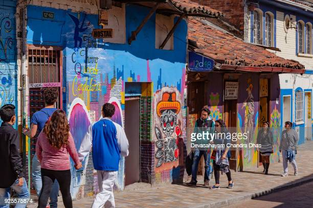Bogotá, Colombia - Local Colombian People Walk Through The Colorful Streets Of The Historic La Candelaria District In The Capital City, In The Afternoon Sunshine