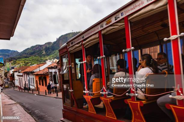 Bogotá Colombia - Local Colombian Tourists on a Tour Bus, modelled on the Old Tram in the Historic La Candelaria District in the Andean Capital City