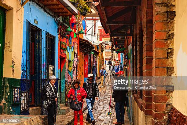 Bogotá, Colombia - Local Colombian Tourists Walk Through The Narrow, Colorful, Cobblestoned Calle del Embudo In The Historic La Candelaria District