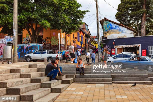 Bogotá, Colombia - Local Colombians And Tourists In The Historic La Candelaria District of The Andean Capital City. Background: Calle Del Embudo.