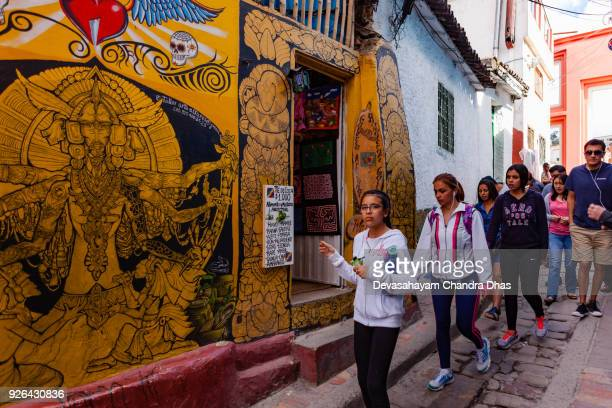 Bogotá, Colombia - Local Colombians And Tourists On The Cobblestoned Calle del Embudo, In The Historic La Candelaria District of The Andean Capital City