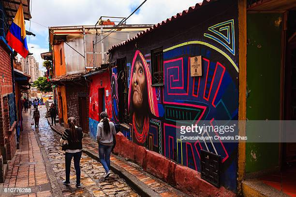 Bogotá, Colombia - Local Colombians Walk Through The Narrow, Colorful, Cobblestoned Calle del Embudo In The Historic La Candelaria District