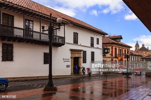 Bogotá Kolumbien - Blick über Calle 11 im Stadtteil La Candelaria, in Richtung zum Eingang in die Casa de Moneda. Regen und spanische Kolonialarchitektur