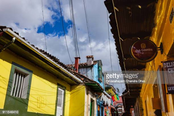 Bogotá, Colombia - Looking Up On The Narrow, Old, Colorful Calle Del Embudo: Spanish Colonial Architecture, Terracotta TIles, Power Cables and A Couple of Chimneys