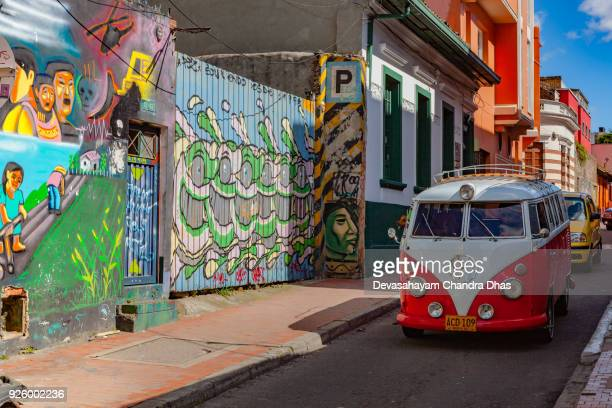 Bogotá, Colombia - Old Volkswagen Mini Van Drives Through A Narrow, Colorful Street In The Historic La Candelaria District In The Capital City