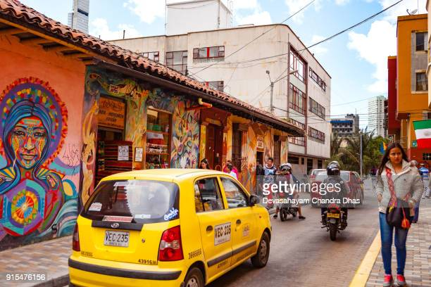 Bogotá, Colombia - People and Traffic On One Of The Colorful Streets In The Historic La Candelaria District In The Capital City.