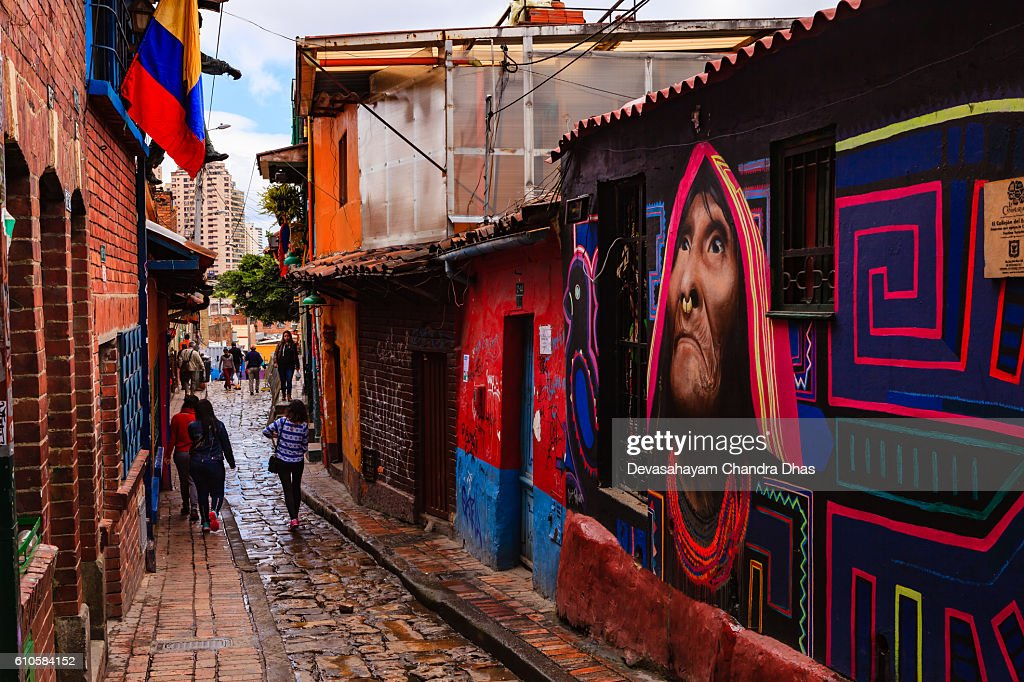 Bogotá, Colombia - People Walk Through The Narrow, Colorful, Cobblestoned Calle del Embudo In The Historic La Candelaria District : Stock Photo