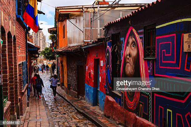Bogotá, Colombia - People Walk Through The Narrow, Colorful, Cobblestoned Calle del Embudo In The Historic La Candelaria District