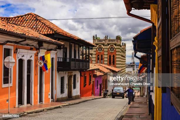 bogotá colombia - arquitectura colonial, paredes coloridas y calles estrechas en el histórico de la candelaria en la capital andina - bandera colombiana fotografías e imágenes de stock