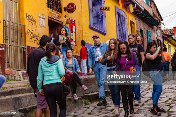 Bogotá, Colombia - Tourists And Local Colombians On The Narrow, Cobblestoned Calle Del Embudo In The Historic La Candelaria District Of the Andes Capital City