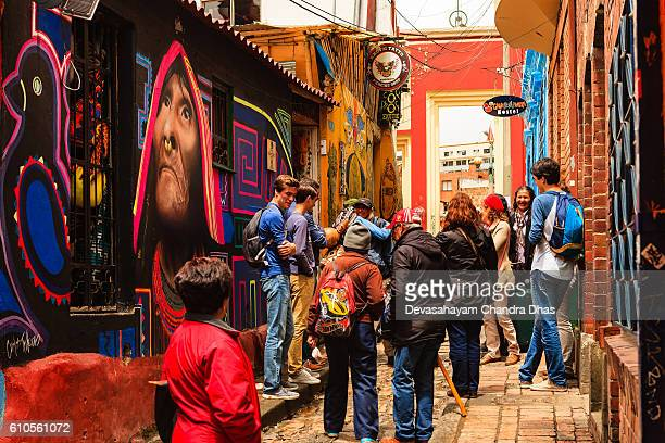 Bogotá, Colombia - Tourists, Both Foreign and Colombian, On The Narrow, Colorful, Cobblestoned Calle del Embudo In The Historic La Candelaria District
