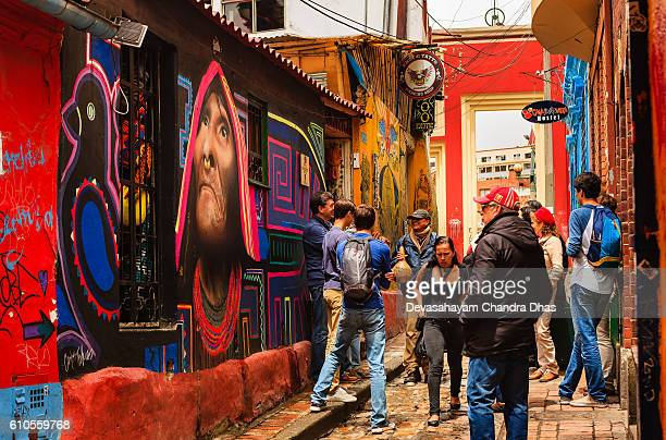 Bogotá, Colombia - Tourists, Both Foreign and Colombian, Walk Through The Narrow, Colorful, Cobblestoned Calle del Embudo In The Historic La Candelaria District