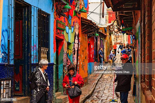 Bogotá, Colombia - Tourists On the Narrow, Colorful, Cobblestoned Calle Del Embudo In The Historic La Candelaria District Of The Capital City