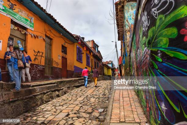 Bogotá, Colombia - Tourists, On The Narrow, Colorful, Cobblestoned Calle del Embudo In The Historic La Candelaria District