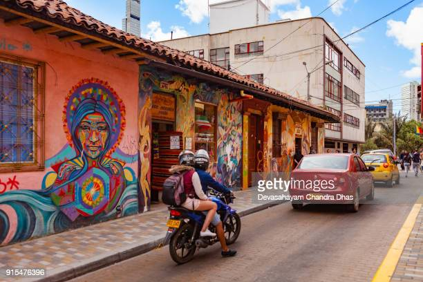 Bogotá, Colombia - Traffic Drives Through The Colorful Streets Of The Historic La Candelaria District In The Capital City