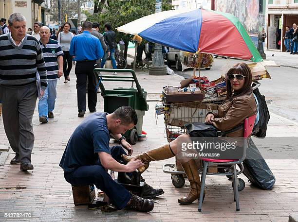 Bogotá Republic of Colombia August 3 2015 A man polish the boots of a woman in the street of Bogota