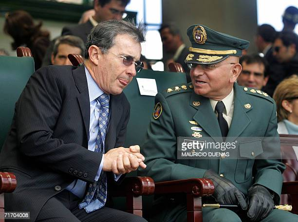 Colombian President Alvaro Uribe speaks with the former Commander of the Armed Forces, Carlos Alberto Ospina, during his farewell military ceremony...