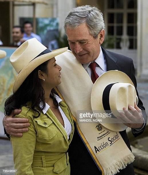 President George W. Bush poses with a woman who presented him with a hat and poncho during a tour on alternative development products 11 March 2007...