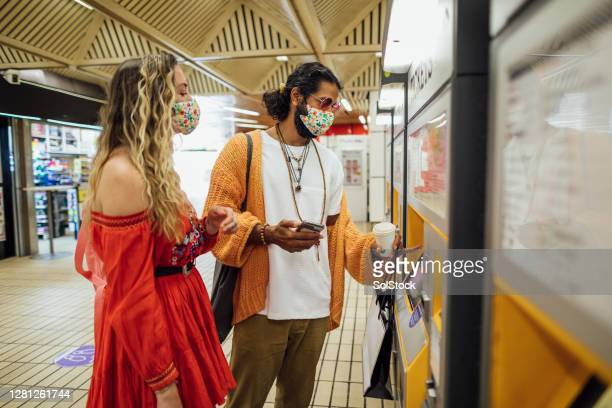 bohemian couple buying their train ticket - rail transportation stock pictures, royalty-free photos & images