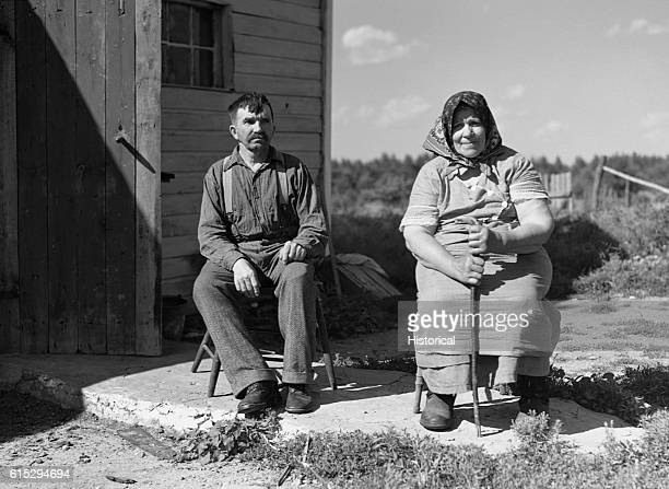 Bohemian farmers of the cutover land area sit in chairs on a small patio in front of their house | Location Black River Falls Wisconsin USA vicinity
