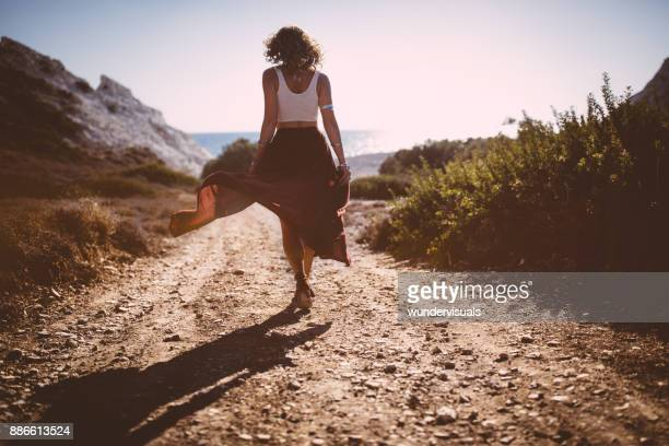 Bohemian girl in skirt and crop top walking in nature