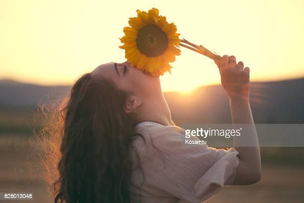 Bohemian Girl Smelling Sunflower