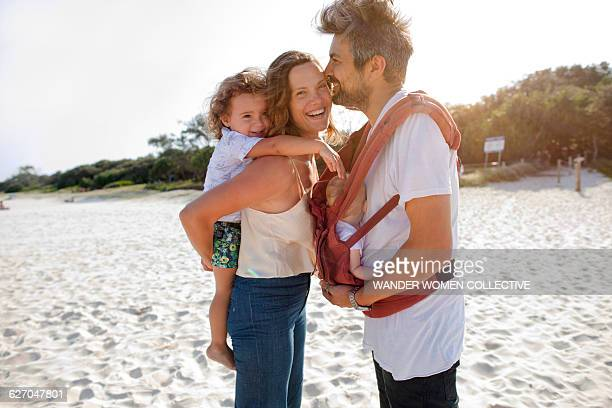 Bohemian hippy family with newborn on the beach