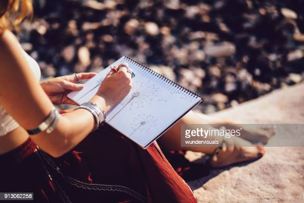 Bohemian woman sketching nature sitting on rock at the beach